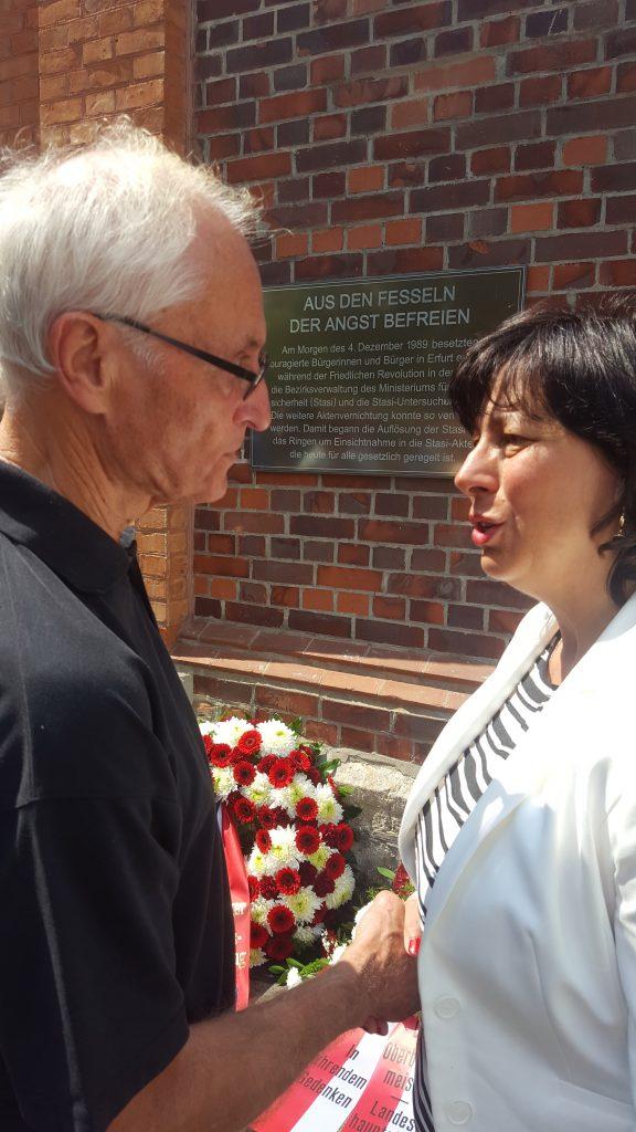 zwei Personen vor einer Gedenktafel