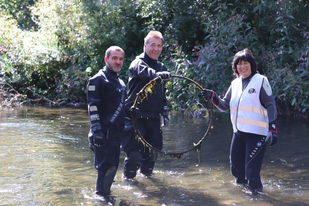 3 Personen sammeln Müll in einem Fluss
